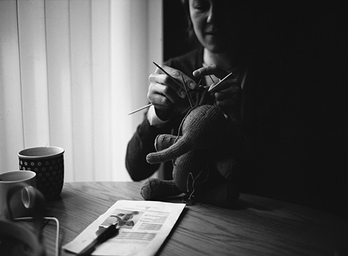 Photo of my sister knitting a stuffed elephant - Shot with the Mamiya m645 on Kodak 100 TMAX film